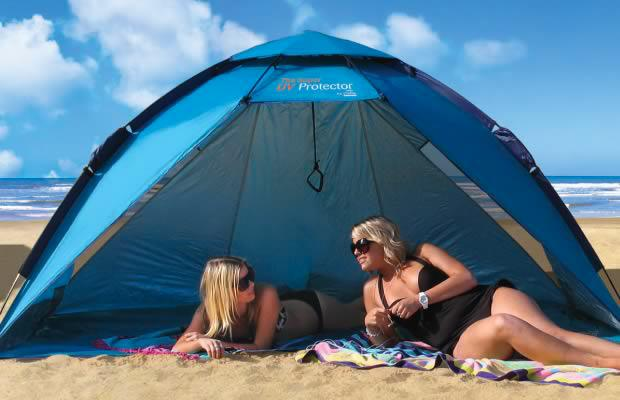 two women at the beach using a beach shelter