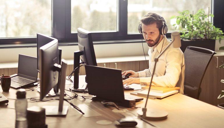 man with headphone facing computer