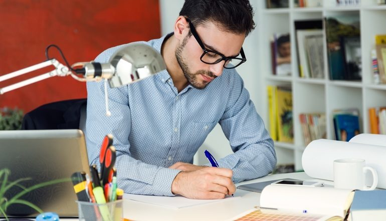 man writing on his notes