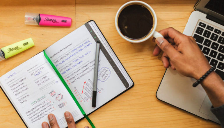 Persons hands on notebook and a cup of coffee