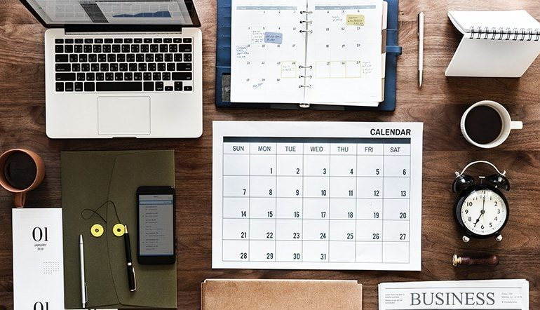 Laptop calendar planner news paper phone on table