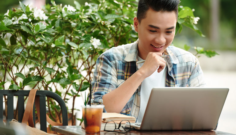 thrilled asian man checking his laptop