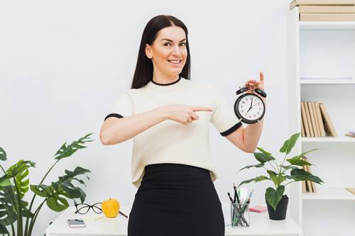 woman smiling while holding alarm clock