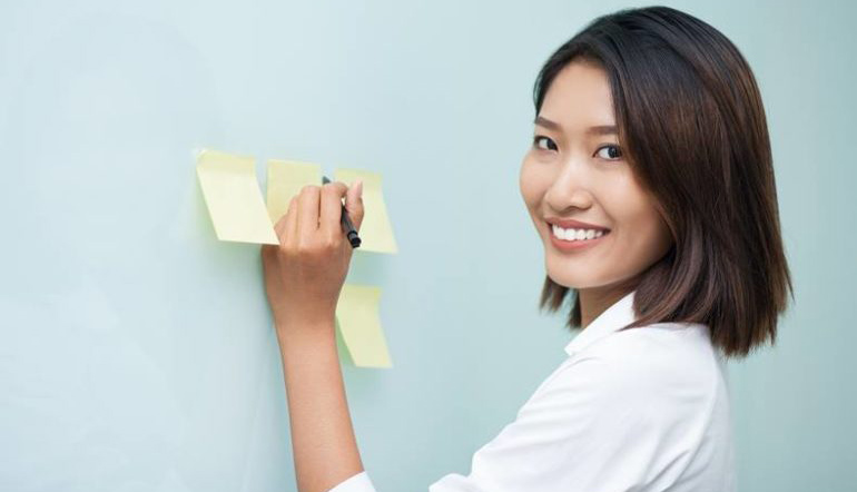 asian woman writing on sticky notes