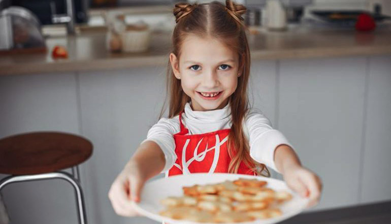 adorable little girl holding plate of cookies