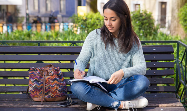 young woman writing on her notebook