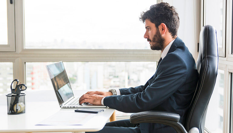 Businessman sitting and working on laptop