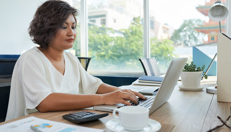 woman with short wavy hair sitting desk office