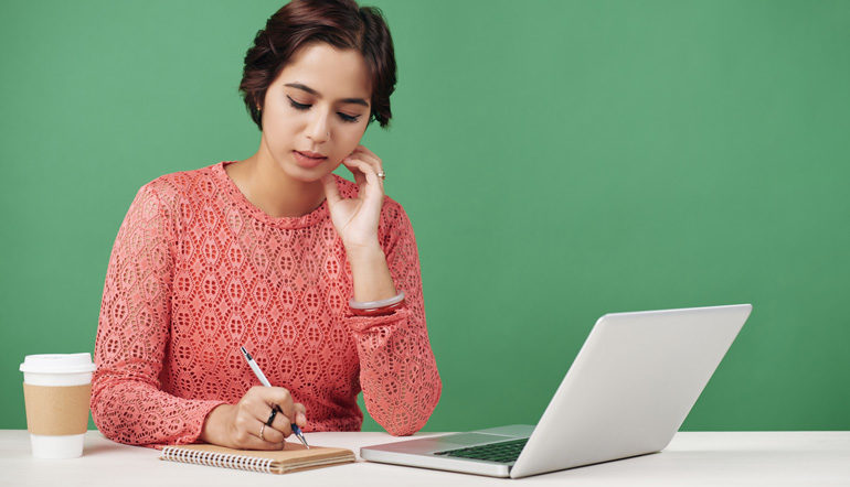 adult woman thinking while writing