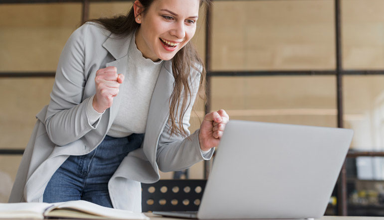 excited adult female looking at her laptop