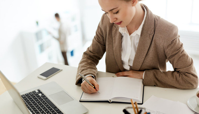 adult female employee writing on her notebook