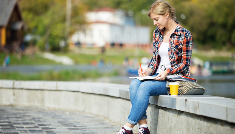 attractive student girl sitting at bridge writing