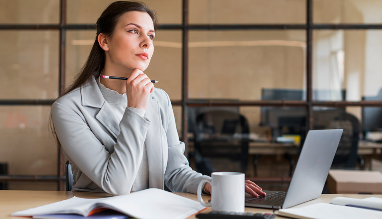 Contemplating businesswoman sitting in front of laptop