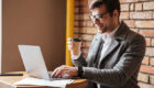 Man reading notes on laptop and drinking coffee