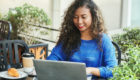 Smiling indonesian businesswoman browsing laptop