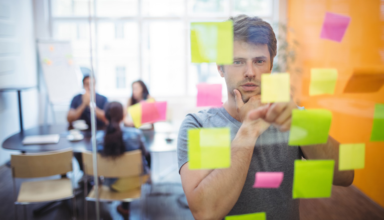 Close-up of male executive reading sticky notes