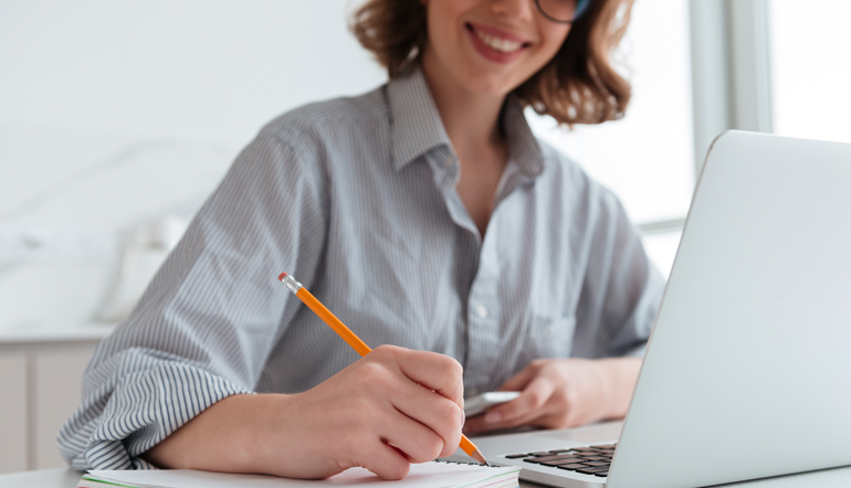 cheerful woman taking down notes