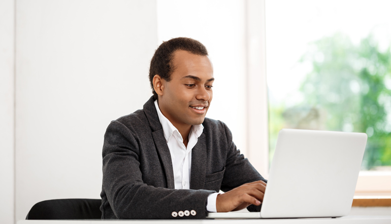 Young successful businessman typing on laptop