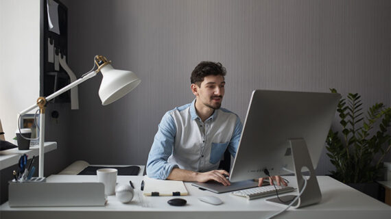 Young man working with his desktop computer