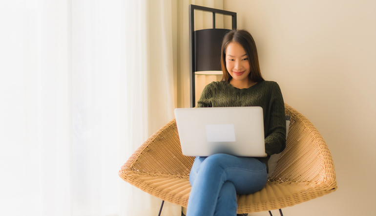 young asian female using laptop