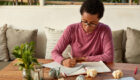 Creative dark skinned writer writes down conclusion of essay