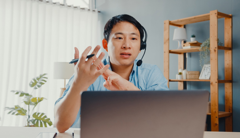 Young asia businessman wear headphones using laptop talk to colleagues