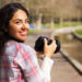 happy young woman holding a camera